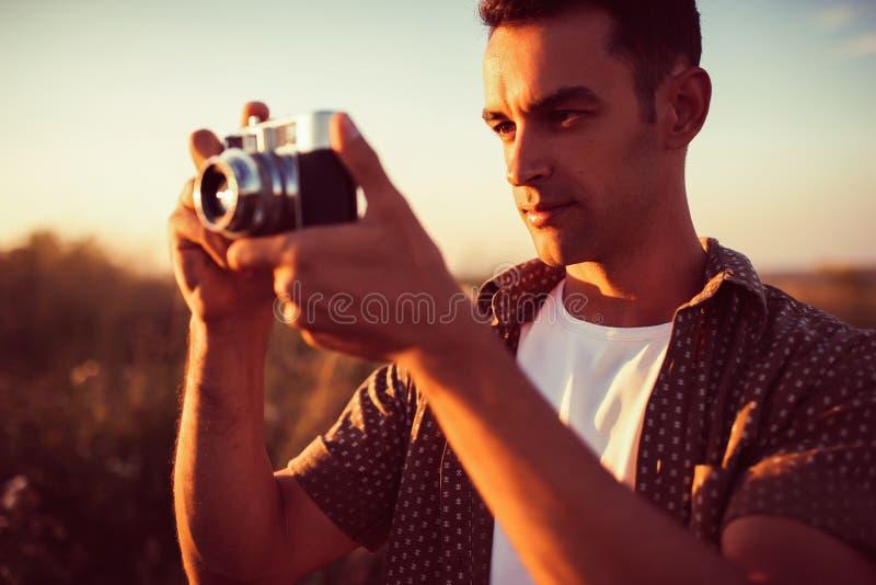 Knap portret van de jonge mooie mens met uitstekende camera op gebiedsachtergrond, royalty-vrije stock fotografie