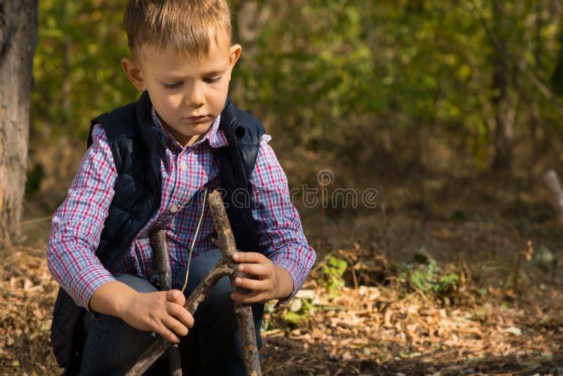Knap weinig jongen die een klein tipi bouwen stock afbeelding