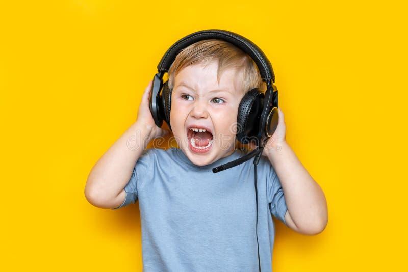 Knap weinig jongen in moderne hoofdtelefoons en het schreeuwen terwijl status op gele achtergrond royalty-vrije stock foto's