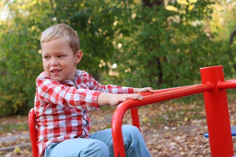 Knap weinig jongen in overhemdsspelen op kleine carrousel stock foto's