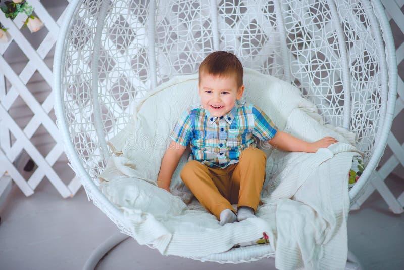 Knap weinig jongenszitting op schommeling het glimlachen het stellen in de Studio royalty-vrije stock foto's