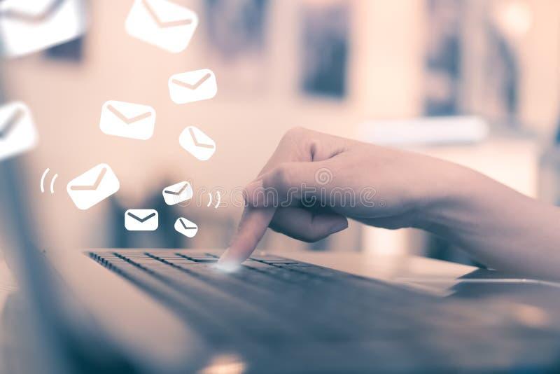 Knapp för tangent för kvinnahandpush på hennes bärbar dator som överför emailen royaltyfria bilder