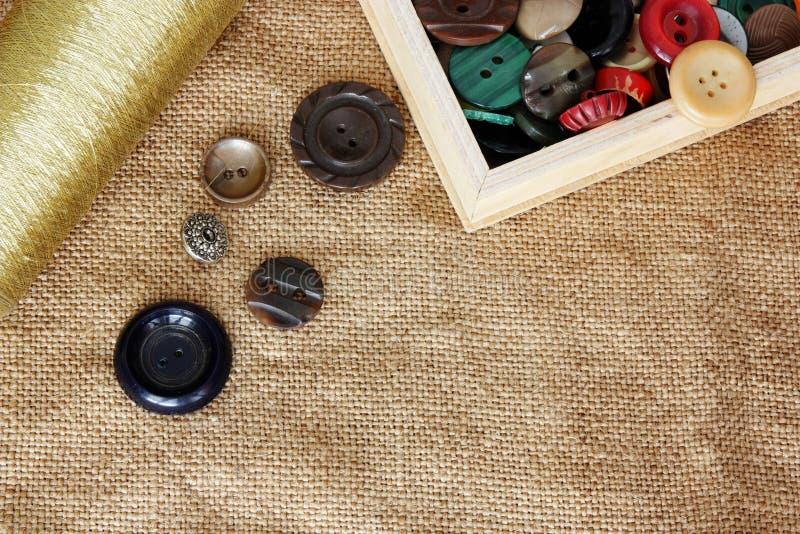 Knappar och rulle av tråden på säckvävbakgrund arkivbild