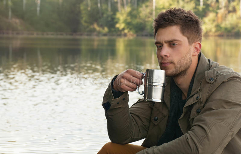 Knappe aantrekkelijke mens bij het meer op mooie aardbackgrou royalty-vrije stock foto