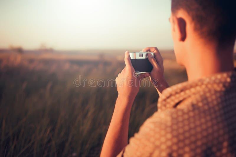 Knappe achtermening van een jonge mens met uitstekende camera, op zonsondergang en gebiedsachtergrond De herfststemming en de zom royalty-vrije stock afbeelding