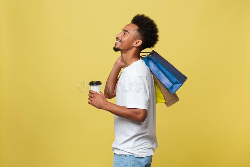 Knappe Afrikaanse Amerikaan met het winkelen zak en haalt koffiekop weg Geïsoleerd over gele gouden achtergrond stock foto's