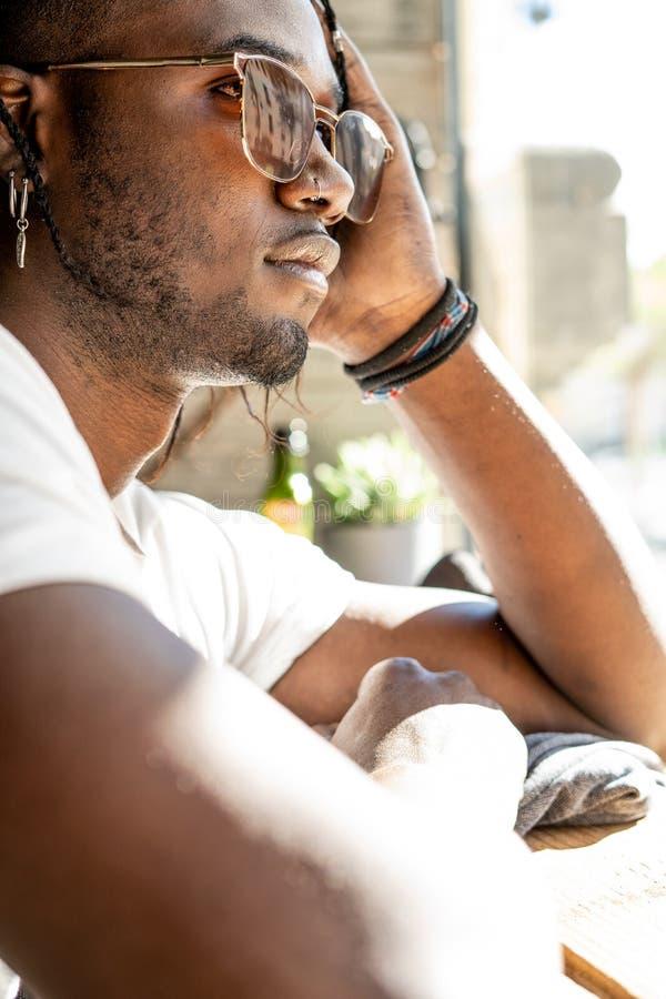 Knappe Afrikaanse Amerikaanse kerel met nadenkende uitdrukking openlucht stock afbeelding