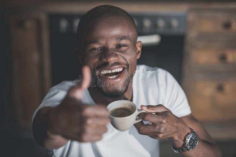 Knappe Afrikaanse Amerikaanse mens die duim tonen en zijn ochtendkoffie hebben stock afbeeldingen