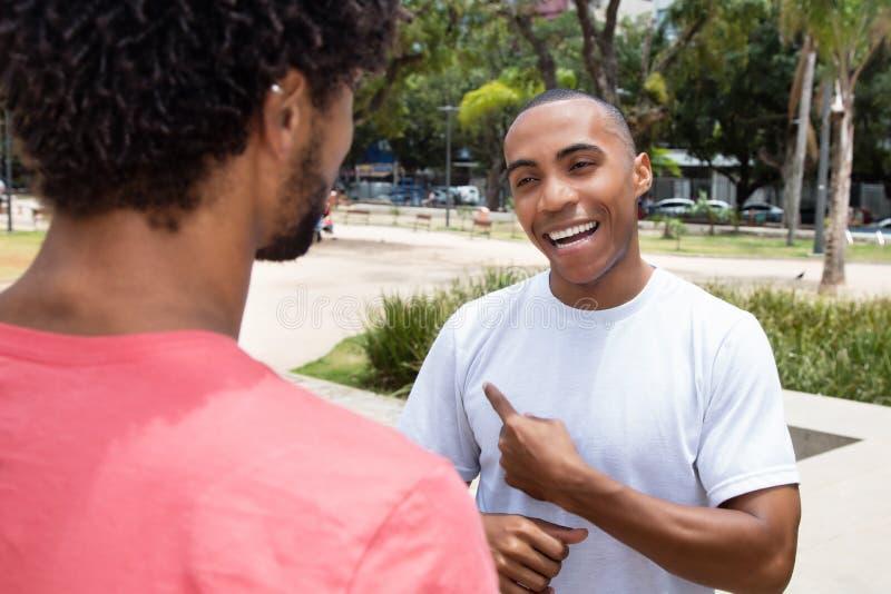 Knappe Afrikaanse Amerikaanse mens die met vriend spreken royalty-vrije stock afbeeldingen