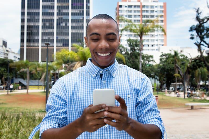 Knappe Afrikaanse Amerikaanse mens die tekstbericht met smartpho verzenden stock foto