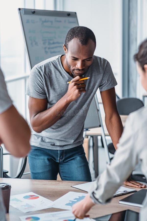 Knappe Afrikaanse Amerikaanse mens die zich door het bureau bevinden en over nieuw bedrijfsproject denken royalty-vrije stock foto's