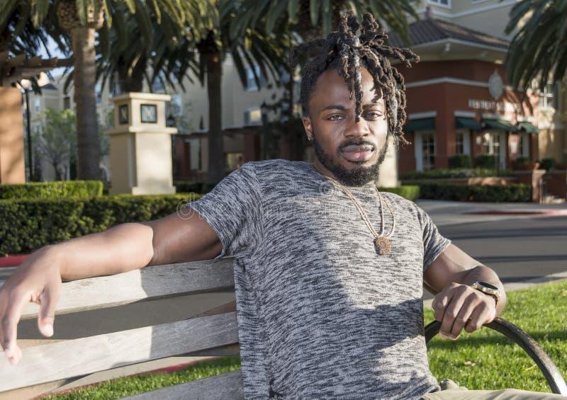 Knappe Afrikaanse Amerikaanse Mensenzitting in het Park royalty-vrije stock fotografie