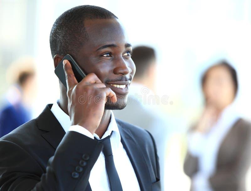 Knappe Afrikaanse Amerikaanse zakenman die op mobiele telefoon spreekt stock afbeeldingen
