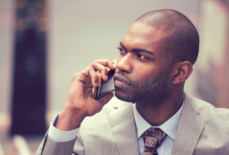 Knappe Afrikaanse Amerikaanse zakenman die op mobiele telefoon spreekt stock fotografie