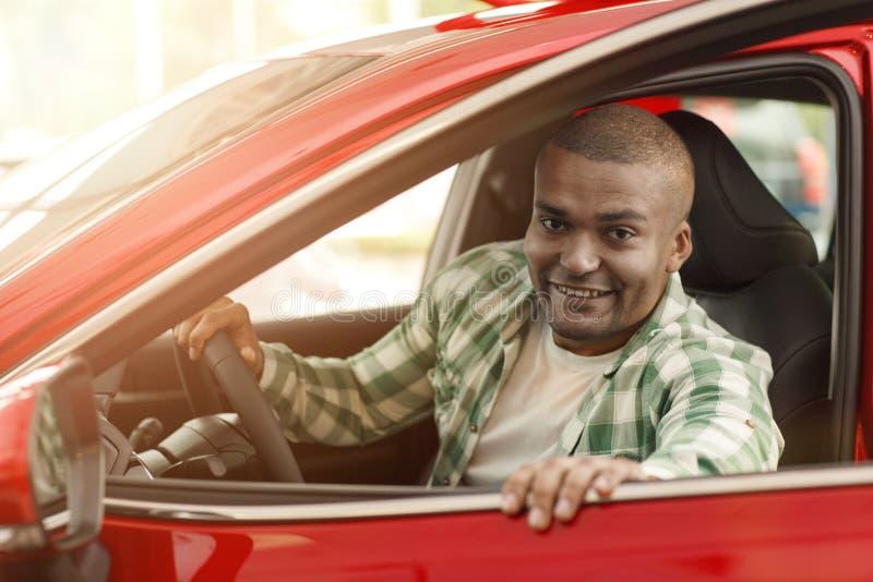 Knappe Afrikaanse mens die nieuwe auto kiezen bij het handel drijven stock fotografie