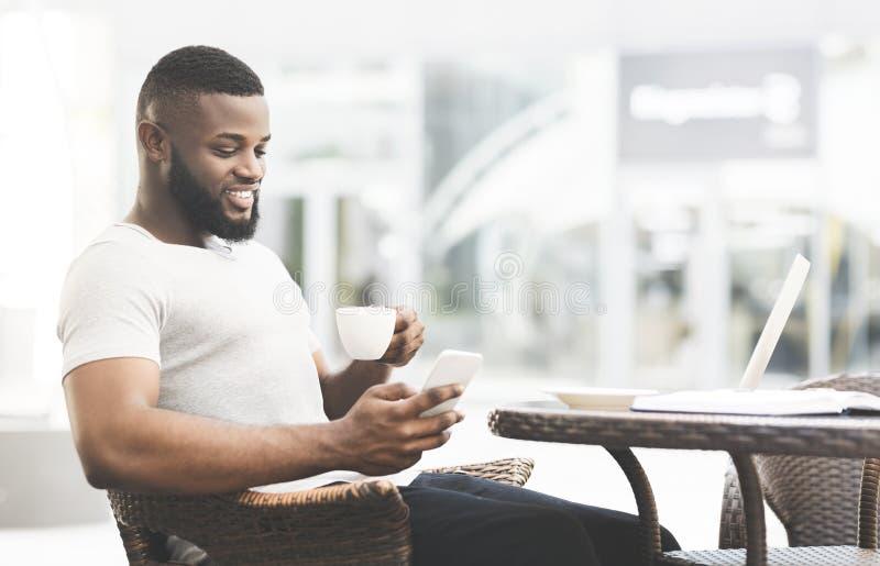 Knappe Afrikaanse mens het drinken koffie en het lezen royalty-vrije stock afbeelding