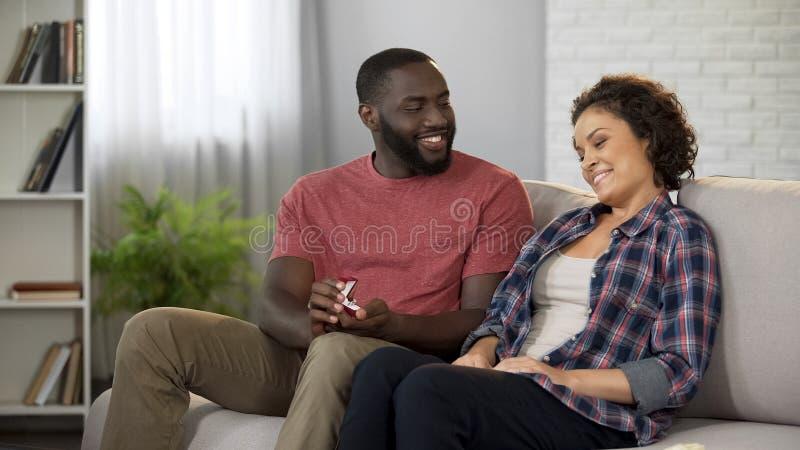Knappe Afro-Amerikaanse man die verlovingsring geven aan zijn vrouw, die voorstel doen stock afbeeldingen