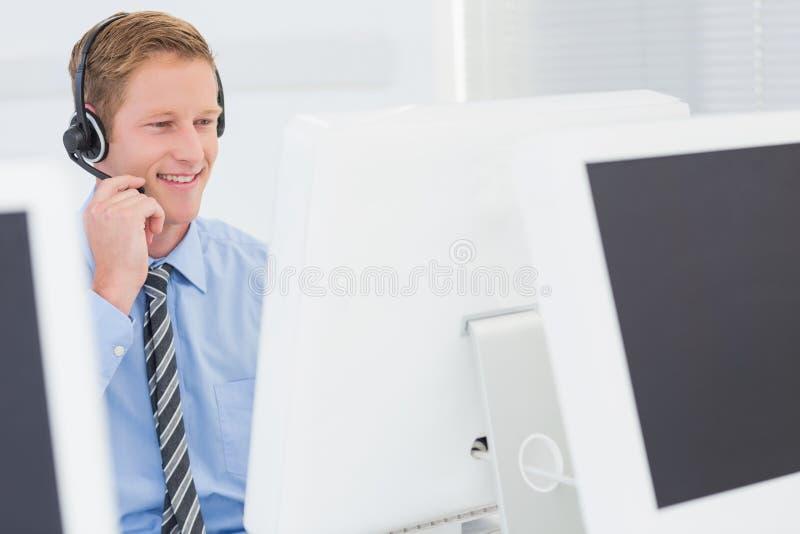 Knappe agent met hoofdtelefoon het typen op toetsenbord royalty-vrije stock afbeelding