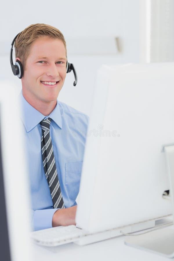 Knappe agent met hoofdtelefoon het typen op toetsenbord stock afbeeldingen