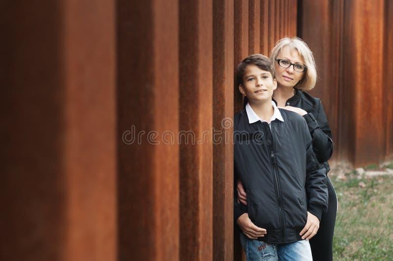 Knappe, alleenstaande oudermamma en tienerzoon in het park foto stock fotografie