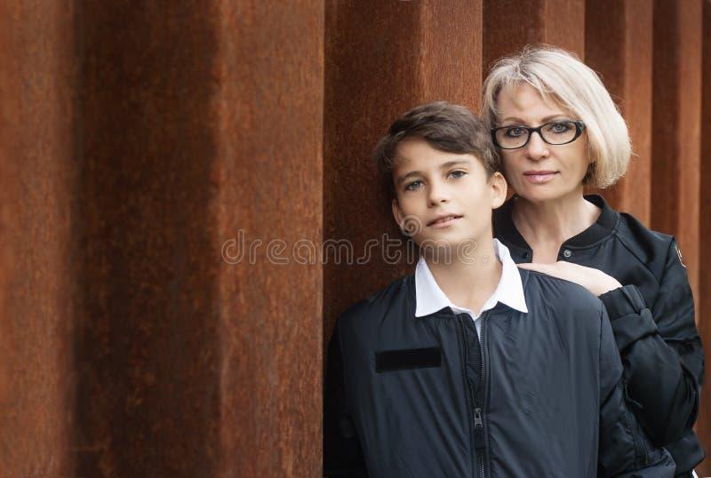 Knappe, alleenstaande oudermamma en tienerzoon in het park foto royalty-vrije stock afbeelding