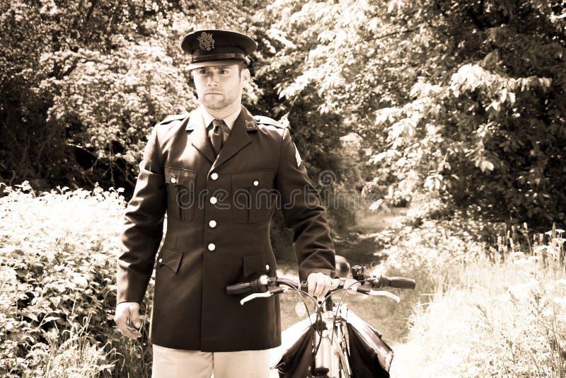 Knappe Amerikaanse WO.II-GI Legerambtenaar in het eenvormige lopen naar huis met zijn fiets royalty-vrije stock afbeelding