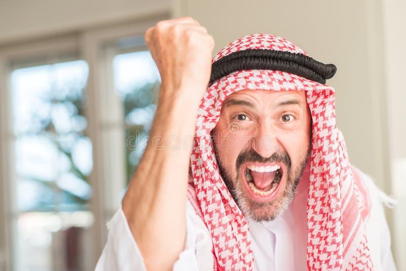 Knappe Arabische hogere mens thuis stock foto