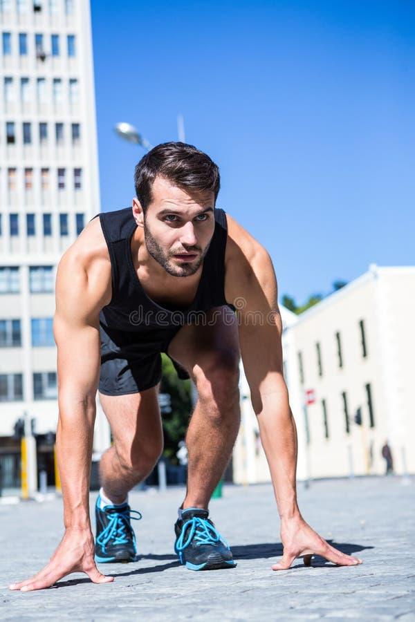 Knappe atleet die klaar aan sprint worden royalty-vrije stock fotografie