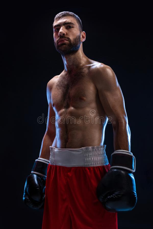 Knappe atletische kerel in rode borrels op een zwarte achtergrond De bokser haalt zijn adem na het praktizeren haken en royalty-vrije stock foto's