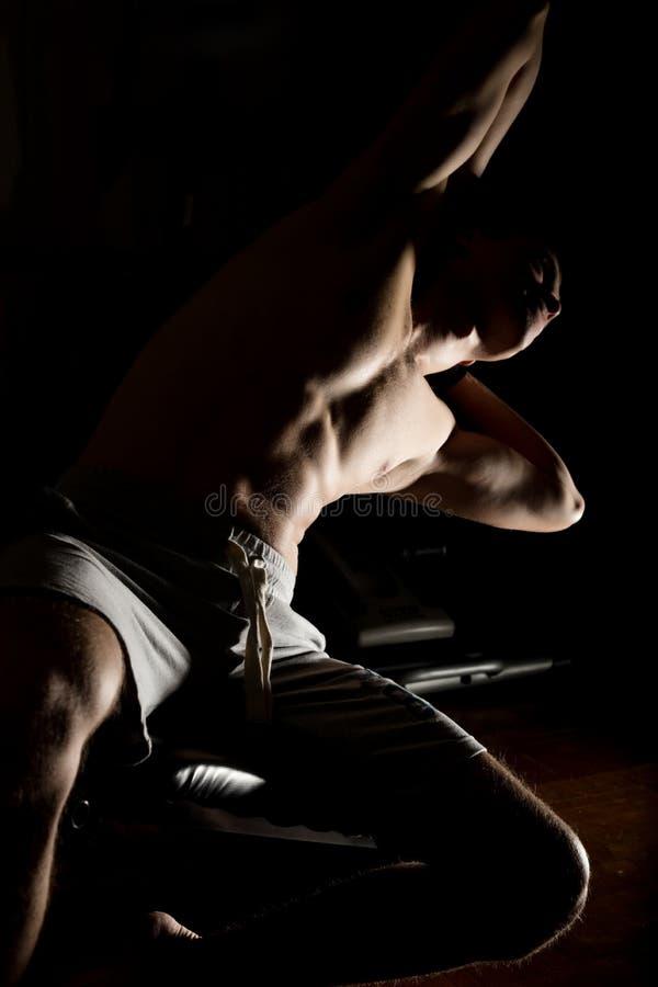 Knappe atletische mens die oefeningen in een gymnastiek op darckachtergrond doen stock foto's