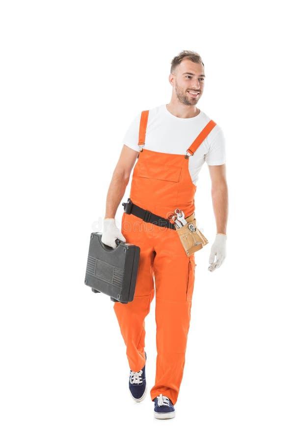 knappe autowerktuigkundige in oranje eenvormige holding toolbox en weg het kijken stock fotografie