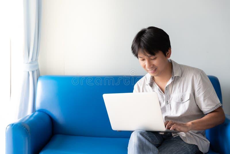 Knappe Aziatische mens die laptop voor de werken en online activiteiten met behulp van terwijl het zitten op blauwe bank royalty-vrije stock afbeeldingen