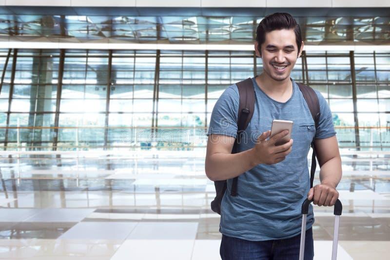 Knappe Aziatische mensenreiziger met smartphone van de kofferholding stock afbeeldingen