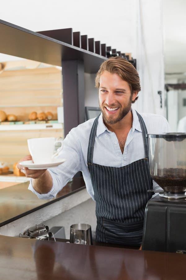 Knappe barista die een kop van koffie aanbieden royalty-vrije stock afbeelding