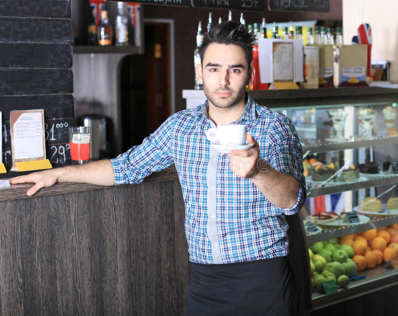 Knappe barista die een kop van koffie aanbieden stock afbeelding