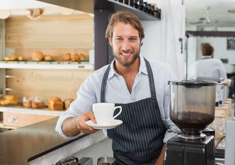 Knappe barista die een kop van koffie aanbieden aan camera stock afbeeldingen