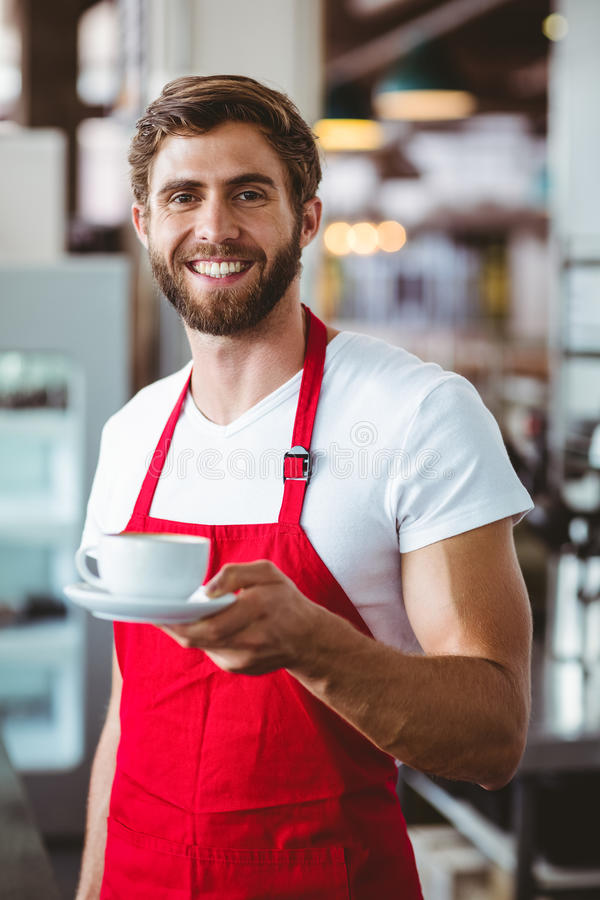 Knappe barista die een kop van koffie houden royalty-vrije stock afbeeldingen