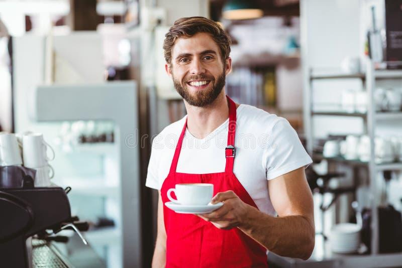 Knappe barista die een kop van koffie houden stock afbeelding