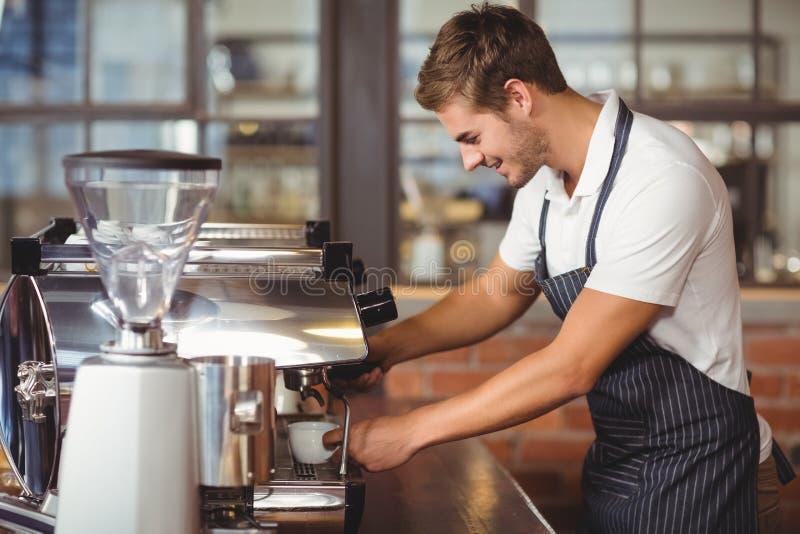 Knappe barista die een kop van koffie maken stock fotografie