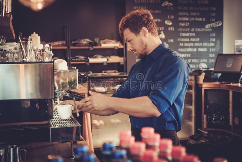 Knappe barista die kop van koffie voor klant in koffiewinkel voorbereiden royalty-vrije stock foto's