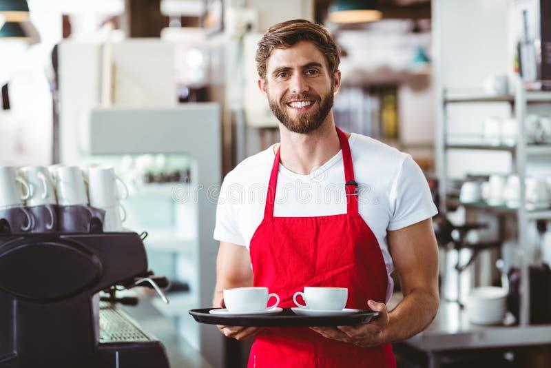 Knappe barista die twee koppen van koffie houden stock foto's