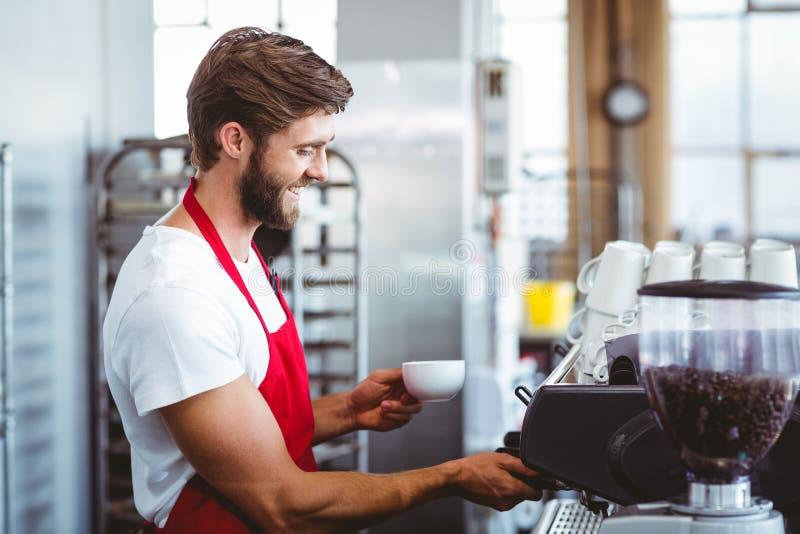 Knappe barista gebruikend de koffiemachine stock fotografie