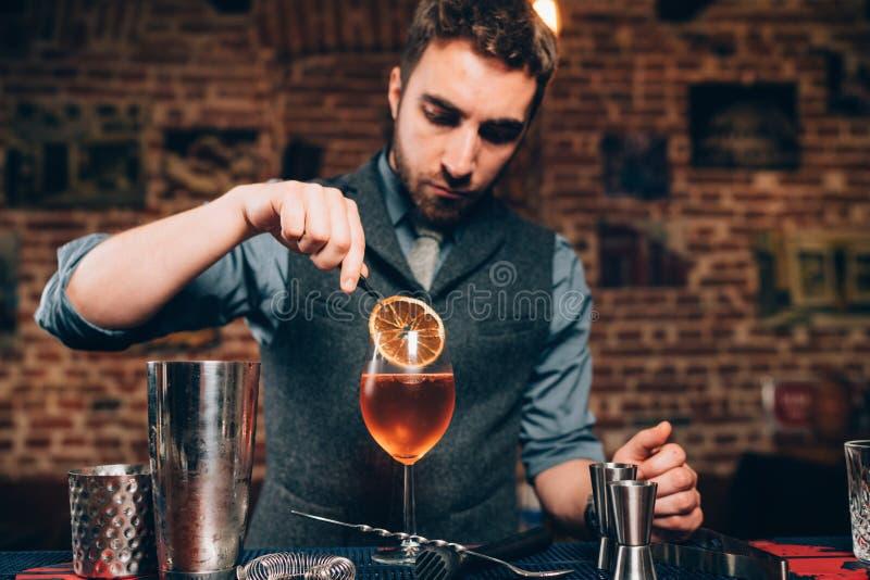 Knappe Barman die alcoholisch aperitief, aperol spritz cocktail voorbereiden stock foto's