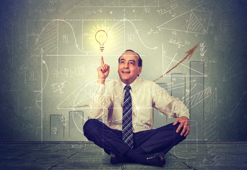 Knappe bedrijfsmens die op gloeilamp richten Het uitvoerende denken over zijn strategie stock afbeelding