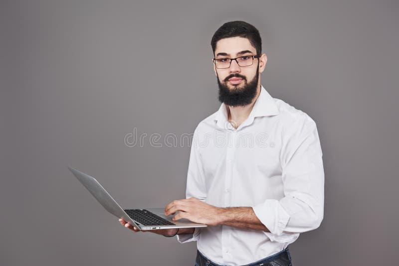 Knappe bedrijfsmens in glazen en laptop van de kostuumholding in handen en het schrijven van iets Zachte nadruk Geïsoleerde grijs royalty-vrije stock afbeeldingen