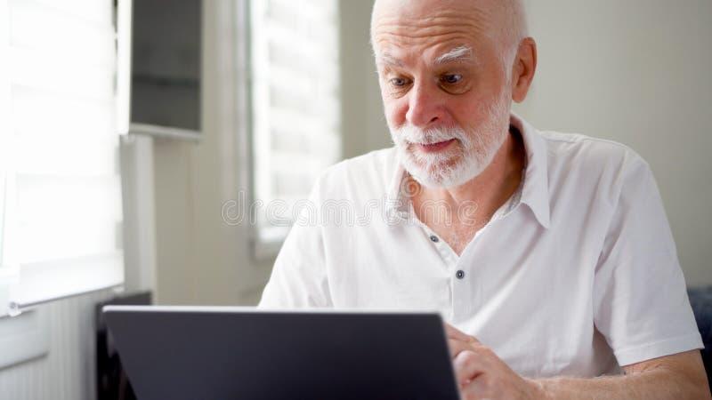 Knappe bejaarde hogere mens die aan laptop computer thuis werken Het verre freelance werk aangaande pensionering royalty-vrije stock foto's