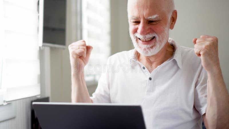 Knappe bejaarde hogere mens die aan laptop computer thuis werken Ontvangen goed opgewekt en gelukkig nieuws royalty-vrije stock fotografie
