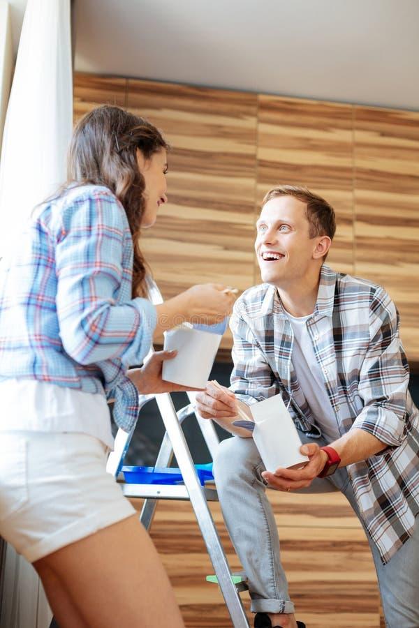 Knappe blauw-eyed echtgenoot die vrouw bekijkt die noedels eet stock afbeelding