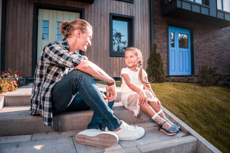 Knappe blonde-haired vaderzitting op de portiek dichtbij zijn leuk meisje stock foto