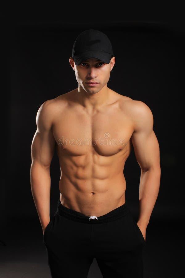 Knappe bodybuildermens met een naakt torso die spieren tonen stock foto's